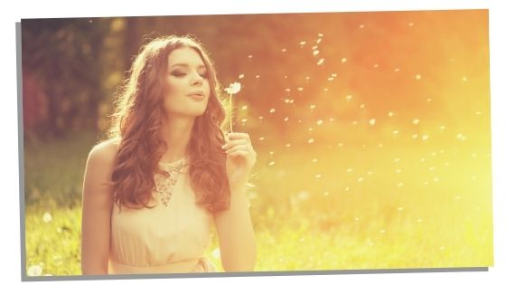 Woman blowing dandelion thinking of blessing